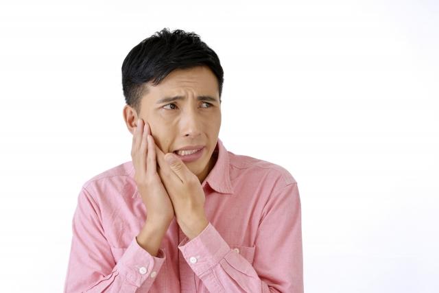 親知らず抜歯後予想外のトラブルが起き困っている男性の写真