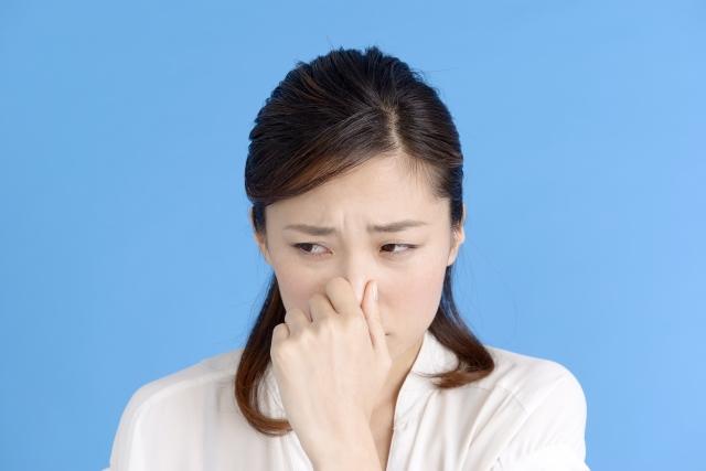 口が臭いと鼻をつまんでいる女性