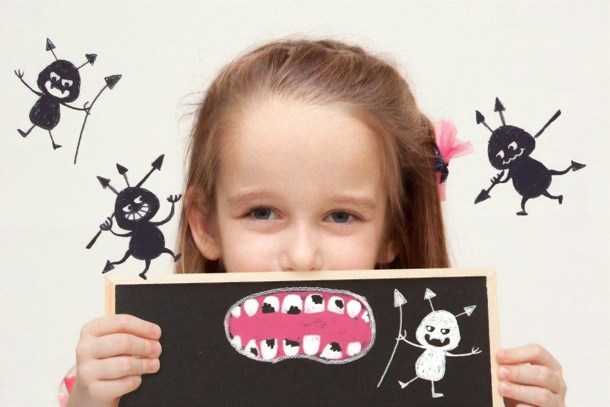 虫歯のイラストを持つ女の子