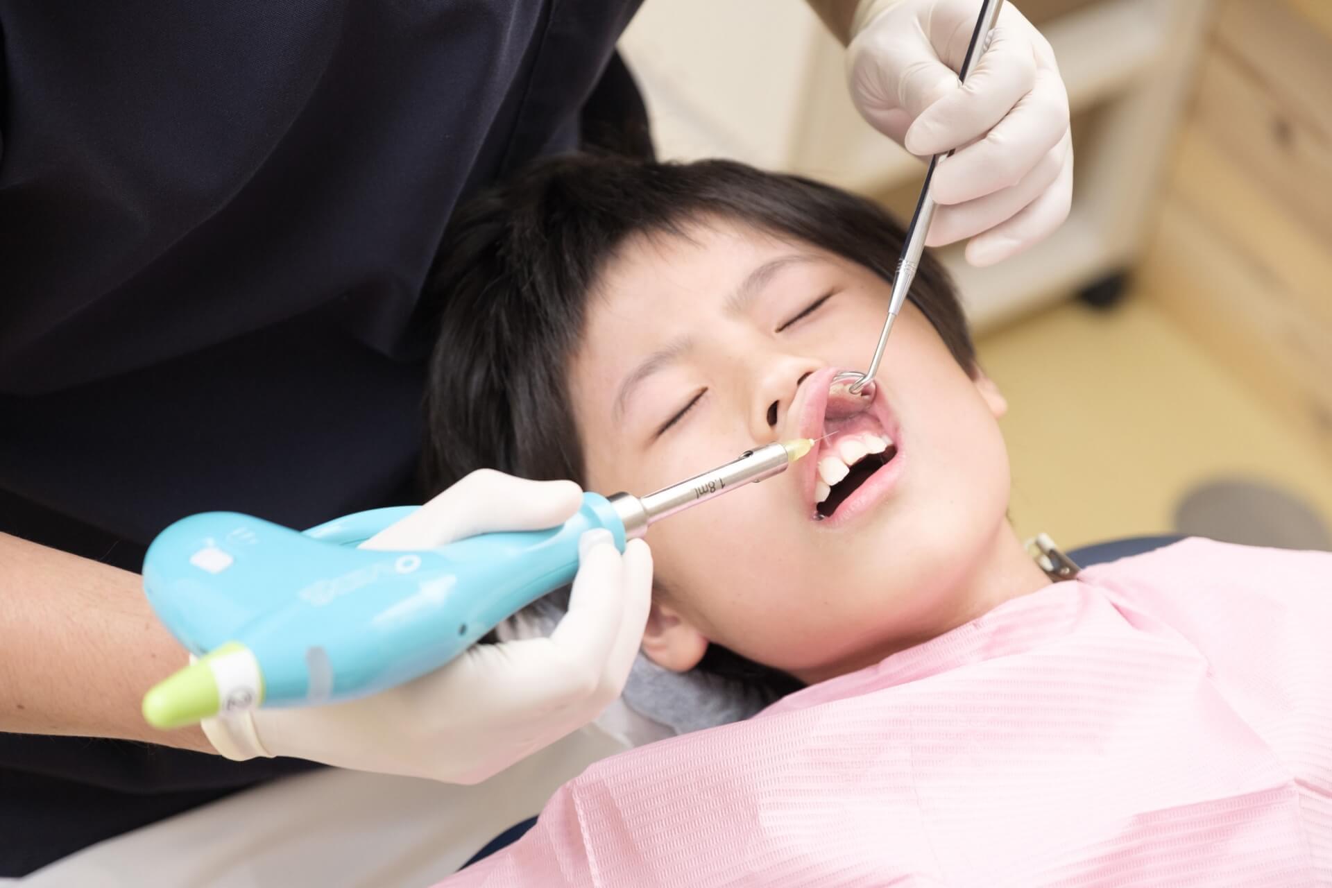 歯の局所麻酔の処置を受けている子供