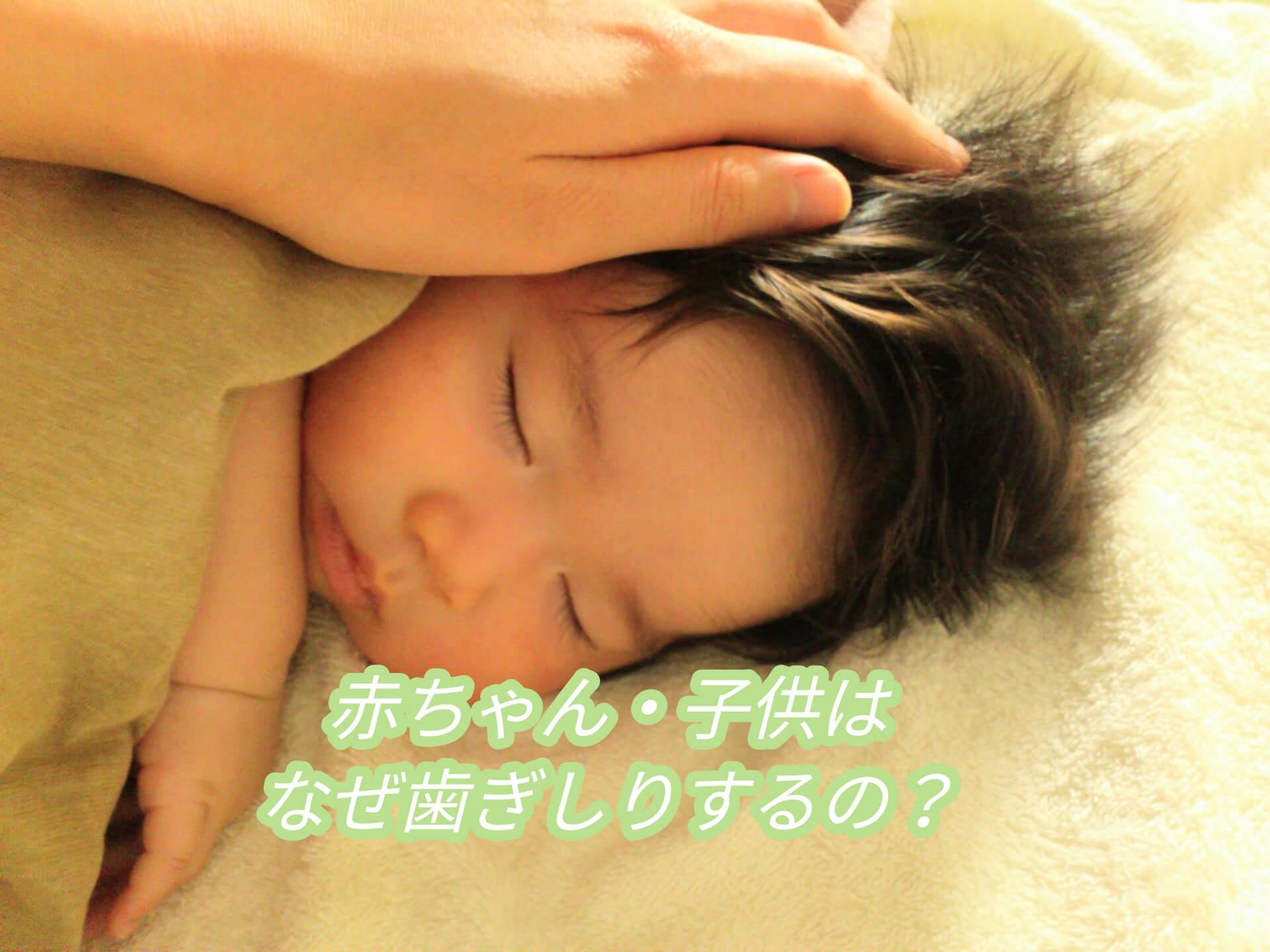 歯ぎしりしている赤ちゃんの心配をするお母さんの手